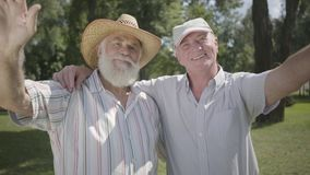 Two positive old men looking in the camera waving hands in the park. Leisure outdoors. Mature people resting in the. Two positive old men looking in the camera stock video