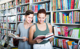 Two positive teenagers reading book together in shop Royalty Free Stock Photos