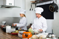 Two positive women chefs cooking food at kitchen Stock Images