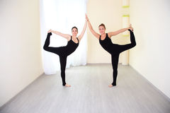 Two positive women, dressed in sportswear practicing yoga. Two sporty women working out in gym, doing yoga exercise. Athletes dressed in a stylish tracksuit royalty free stock images