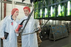 Two positive workers in white coats on beer brewery factory. Bottling Royalty Free Stock Images