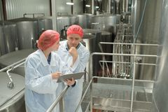 Two positive workers in white coats at factory royalty free stock images