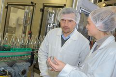 Two positive workers in white coats working at dairy factory. 2 royalty free stock photo
