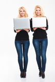 Two positive young blonde sisters twins with laptop computers Stock Images