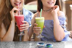 Two positive young women enjoying fresh smoothie. In cafe Stock Photos