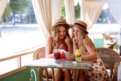 Two positive young women enjoying fresh smoothie in cafe royalty free stock images