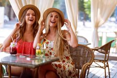 Two positive young women enjoying fresh smoothie in cafe royalty free stock photography