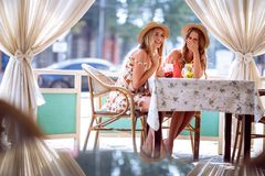 Two positive young women enjoying fresh smoothie in cafe stock photos