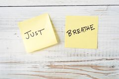 Two Post It Notes with Message Just Breathe. Two yellow Post It notes with message Just Breathe against weathered white wood background Stock Image