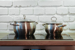 Two pots. On a black cooker with a white rustic wall behind Royalty Free Stock Photo