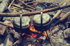 Two pots, covered with soot, are hanging over a campfire Stock Image
