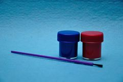 Two pots of paint with a purple paintbrush. On a blue background royalty free stock photo