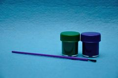Two pots of paint with a purple paintbrush. On a blue background royalty free stock photography
