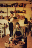 Two potters working with ceramics in atelier. Portrait of two smiling potters working with pottery wheel in ceramics atelier royalty free stock photo