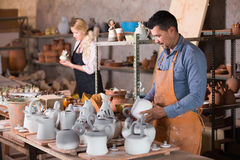 Two potters working in workshop. Man and women potters working in pottery workshop royalty free stock photos