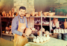 Two potters working in workshop. Professional man and woman potters at the work in pottery royalty free stock photos