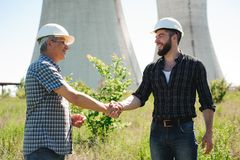 Two power line tower workers with handshaking royalty free stock image