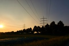 Two power poles and sunrays from a sunset. And a field Stock Photos