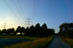Two power poles and sunrays from a sunset stock photo