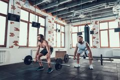 Two Powerful Guys In Gym Are Lifting Barbells royalty free stock photo