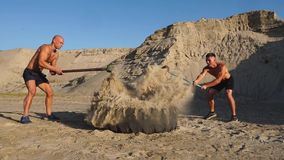 Two powerful male athletes training together hit the wheel with a hammer at sunset in the desert. Endurance training.  stock video footage