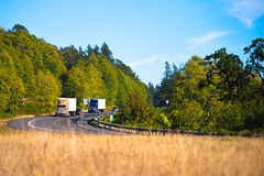 Two powerful semi trucks on winding highway Stock Photography