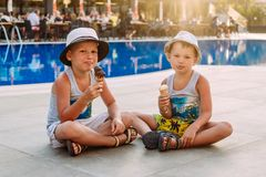 Two pre-school boys in hats sit by the hotel`s outdoor pool and eat ice cream in a waffle cone . Kids and ice cream. Lips in ice stock photo