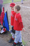 Two pre-teen baseball players discussing the game. Two young boys discussing their grade school baseball game as they are waiting for their turn to go up to bat Royalty Free Stock Photos