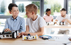 Two pre-teen students socializing during robotics class. Best friends. Lovely pre-teen boys talking to each other during a robotics workshop while their teacher Royalty Free Stock Photo