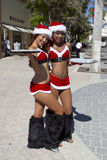 Two preety female Santa Claus offering drinks Stock Image