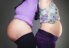 Two pregnant friends are waiting for their children showing bell Royalty Free Stock Images