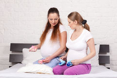 Two pregnant girlfriend. With children's clothes sit on the bed at home Stock Photography