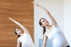 Two pregnant sports models do gymnastic exercises, raising their hands up, yoga pose, Utthita Parsvakonasana Stock Image