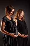 Two pregnant women in black dresses touching their belly and thinking about future Royalty Free Stock Photos