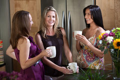 Two Pregnant Women with Friend. Two pregnant women enjoy cup of coffee or tea with their blonde friend Stock Photography