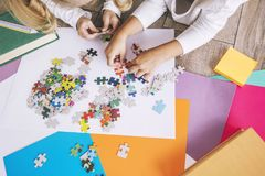 Two preschool age child put the puzzle together on the floor, ha Royalty Free Stock Photos