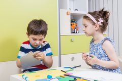 Two preschool child working for homework received from kindergarten Stock Image