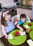 Two preschool children eat strawberry with brown sugar Royalty Free Stock Image