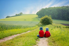 Two preschool children, sitting in the rural, contemplating the Royalty Free Stock Photos