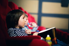 Two preschool children, twin brothers, watching movie in the cin. Ema, eating popcorn Stock Images