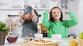 Two preschool girls bakers eats cooked cheesecakes and shows big finger up. Close up stock video