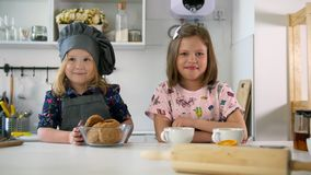 Two preschool girls bakers raising thumbs up. Close up stock video