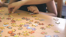 Two preschool girls play a game collecting puzzles. Two preschool girls play a intellectual game collecting puzzles at the table at the kindergarten. Close-up stock video