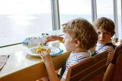 Two preschool kids boys eats pasta sitting in cafe on cruise ship stock photos