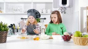 Two preschool little girls bakers playing and have fun during cooking cheesecakes and desserts. Close up stock video footage