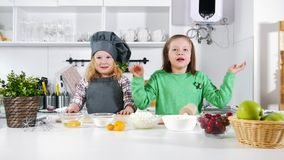 Two preschool little girls bakers waving hands into camera before cooking cheesecakes. Close up stock footage
