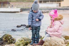 Two preschoolers actively playing on stony beach Stock Photos