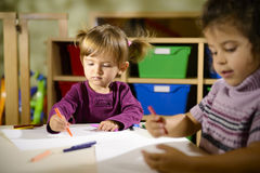 Two preschoolers drawing in kindergarten. Children having fun at school, two happy young girls drawing in kindergarten Stock Photography
