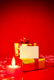 Two presents and blank card. Against red background Stock Image