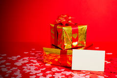Two presents and blank card. Against red background Royalty Free Stock Images